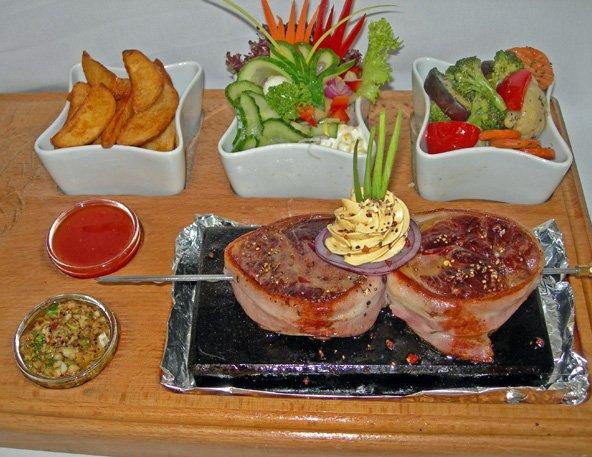 Grillezett ökörbélszín bacon szalonna kalodában forró lávakövön tálalva, gazdagon körítve