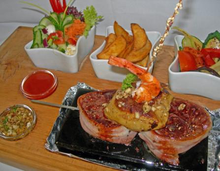 Lávakövön sült bélszínsteak hízott libamájjal, fokhagymás királyrákkal, színes salátákkal, fűszeres steakburgonyával, Cafe de Paris vajban párolt zsenge zöldségekkel